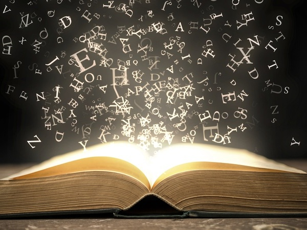 An open book with sparkling gold letters rising from it on a black background