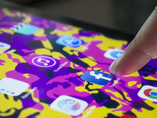 A finger touching Facebook on a colourful smartphone