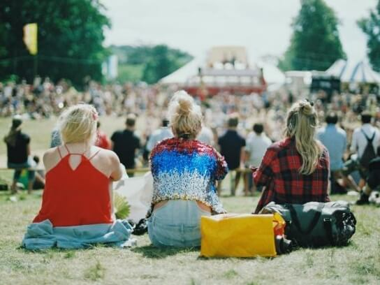 People sat on the grass at a festival in bright clothing
