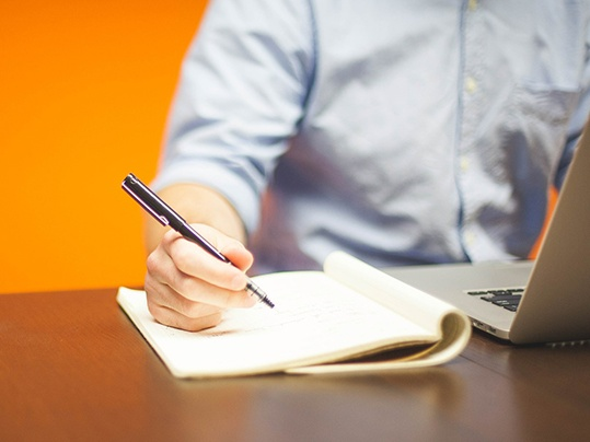 Person writing on a pad with an orange background