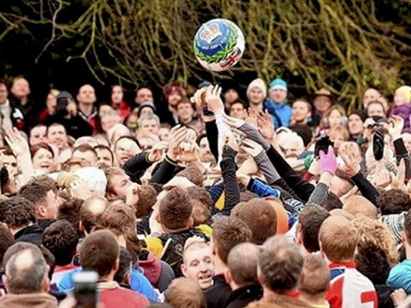group of people in huddle gathered playing shrovetide football