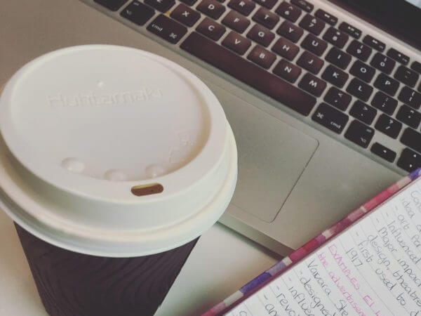 Student doing coursework with coffee, laptop and notes