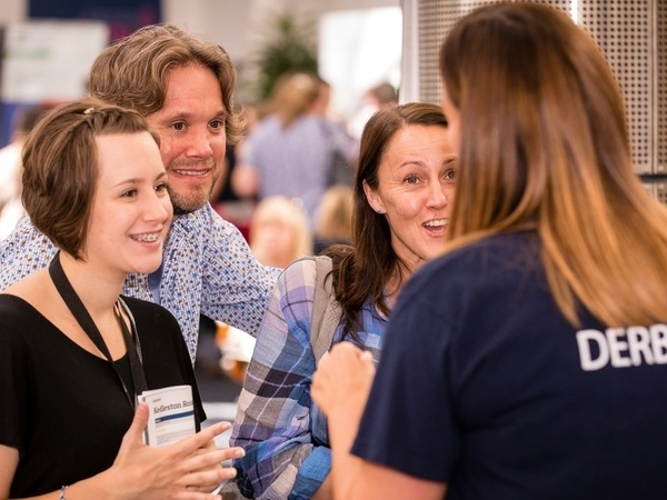 A student ambassador speaking with parents at a University of Derby event