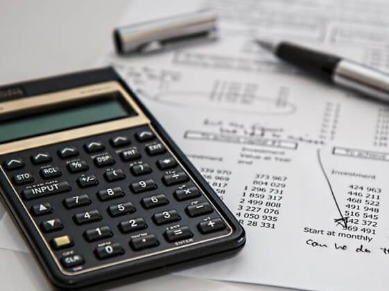 Calculator calculating on a piece of paper and a pen