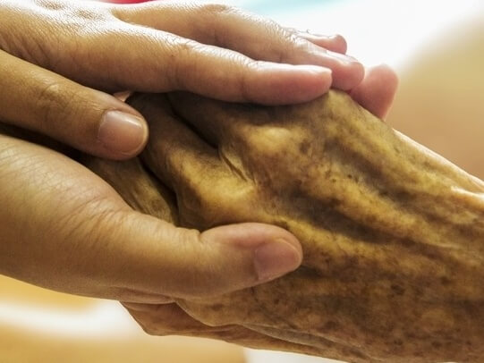 Two hands holding , one elderly