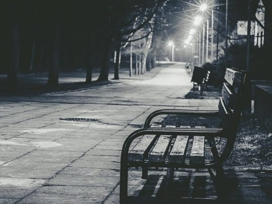 A bench in a street in the dark