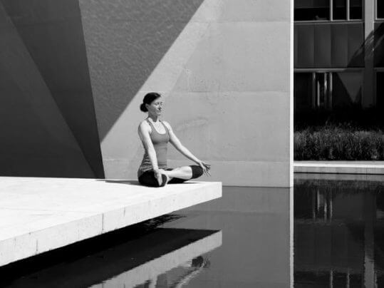 person meditating by a pool