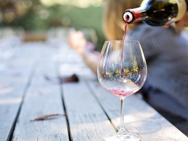 Somebody pouring red wine from a bottle into a glass on a picnic table outdoors