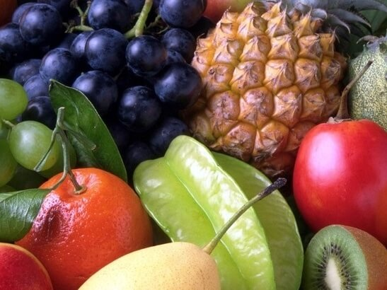 A close up of fruit kiwi pineapple berries  apple