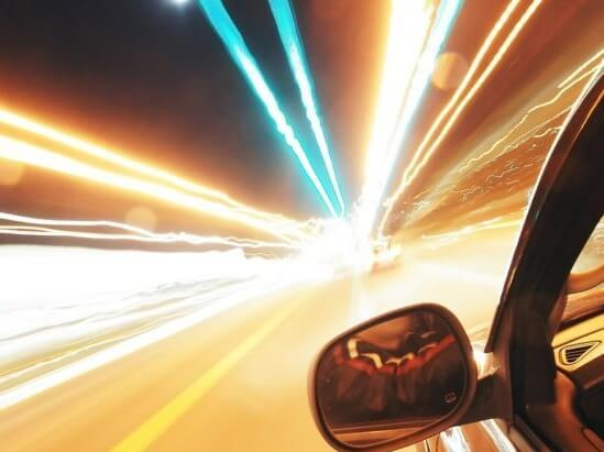 a car driving at night under street lights