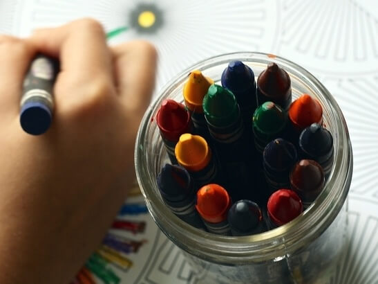 Children drawing with coloured crayons
