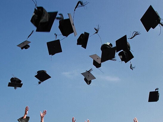 Graduation hats being thrown into the sky.