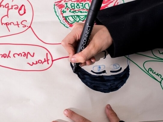 Hand holding a black marker pen and drawing a picture.