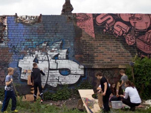 A group of children graffiti a brick wall