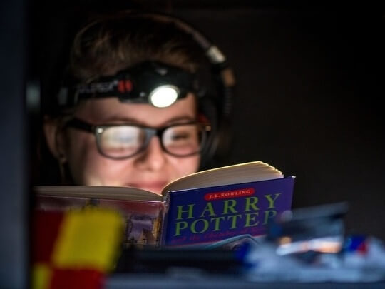 A child reading a harry potter book with a head torch