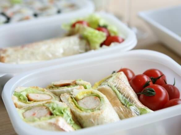 Salad wraps and cherry tomatoes in a plastic lunchbox.