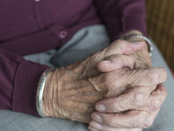 Close-up of an elderly person's hands clasped together