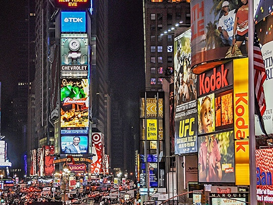 Buildings in Times Square, New York illuminated at night time.