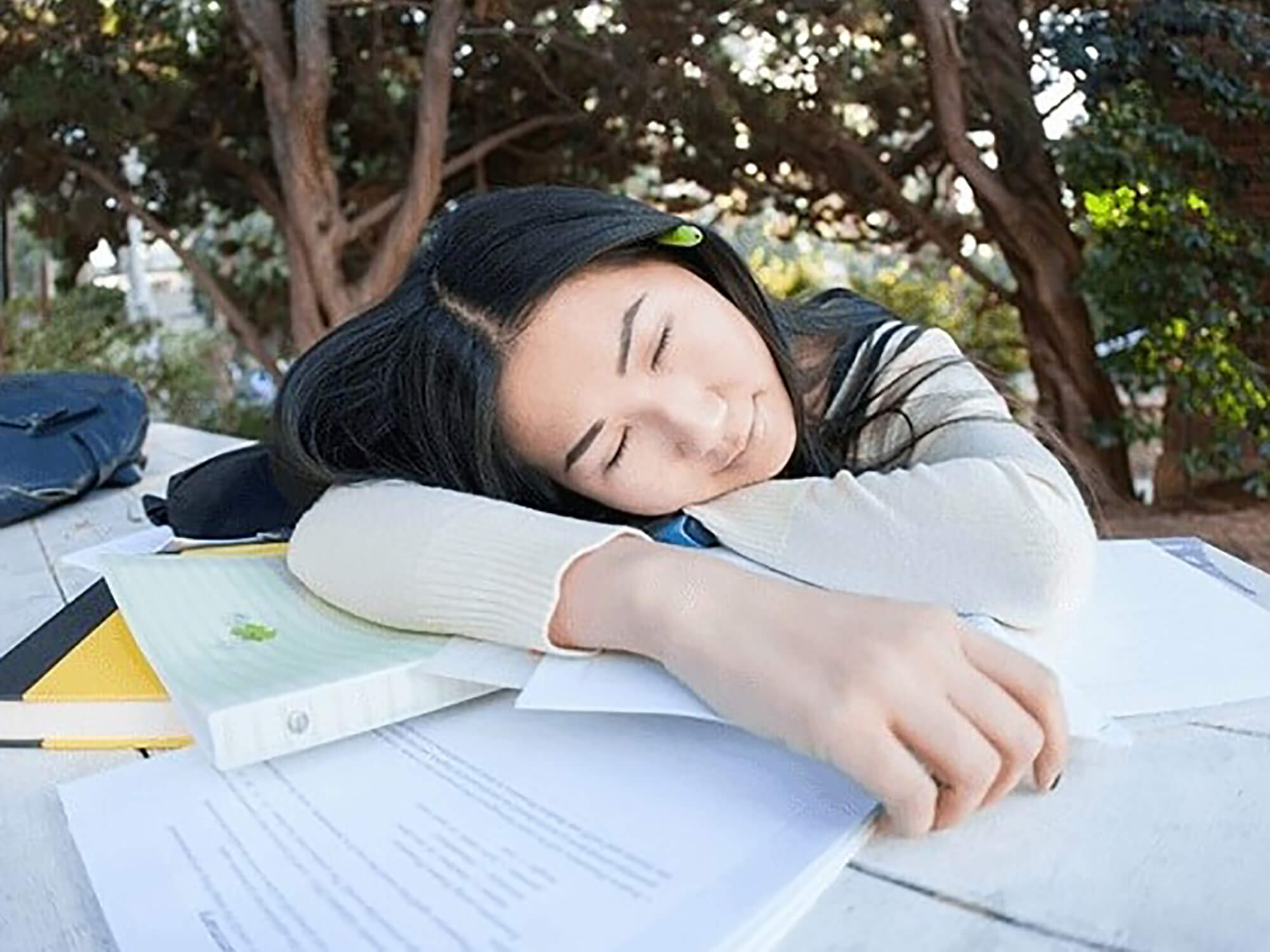 Student rests their head on a table covered in papers.
