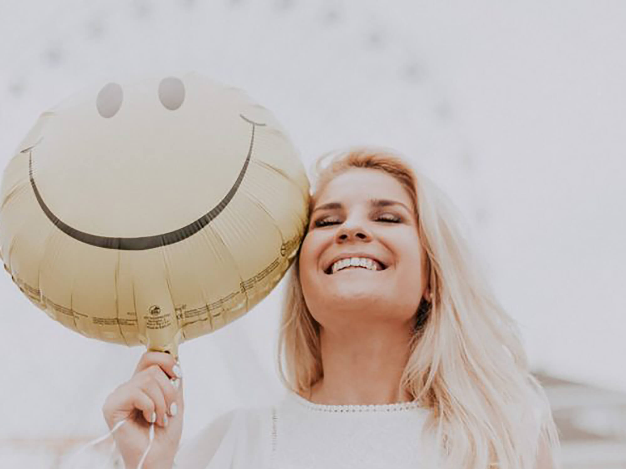 Person holding a smiley face balloon and smiling