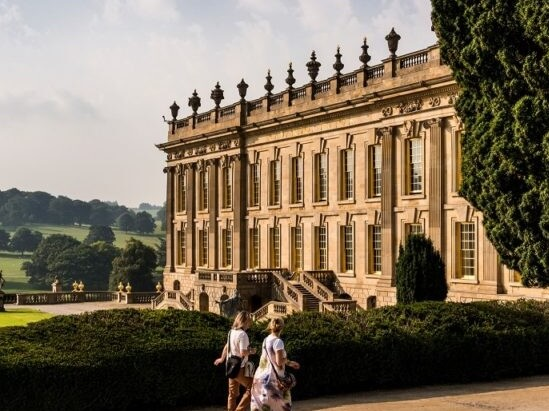 Chatsworth House against a backdrop of rolling, wooded hills