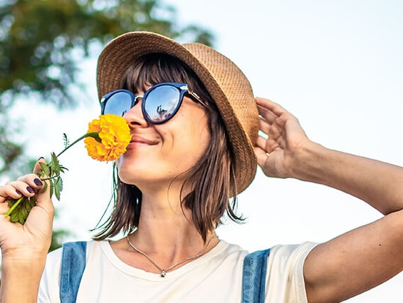 Person with a hat and yellow flower