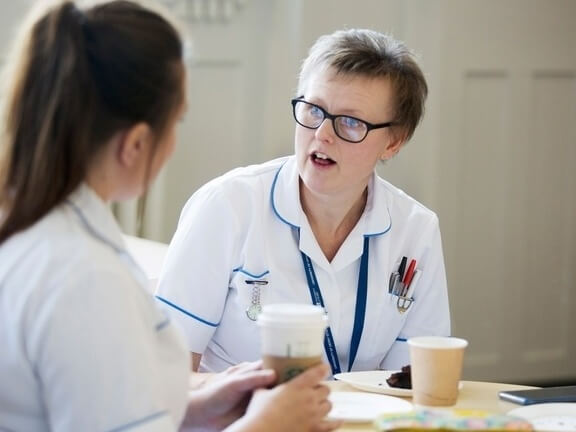 Two nurses chatting over hot drinks at a table.
