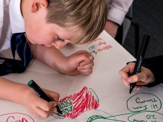 Child drawing with pens on paper