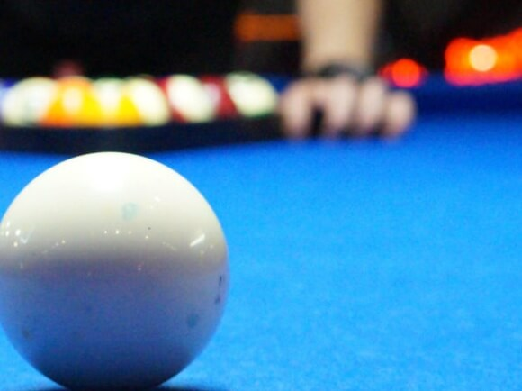 White pool ball on a blue pool table