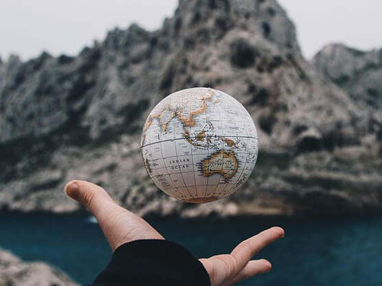 Floating globe over a sea and some rocks.