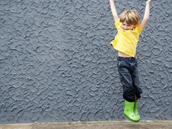 A small child in a yellow tee-shirt and green wellies jumping in front of a grey stucco wall