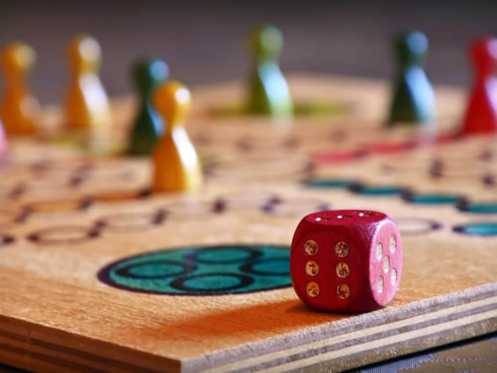 Wooden board game with counters and a dice