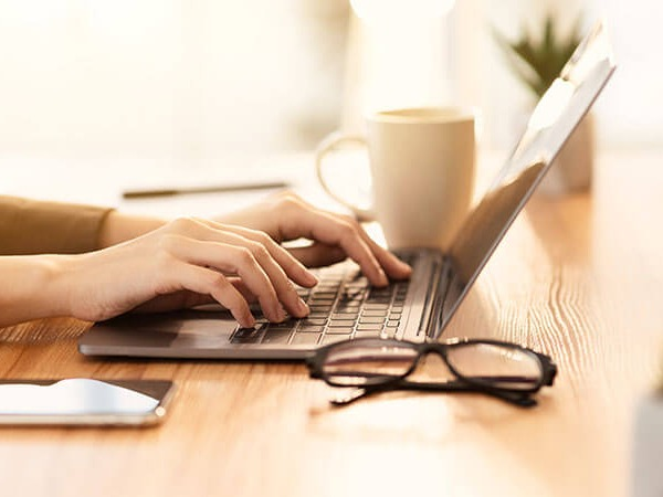 A side image of a desktop with an open laptop with a pair of hands typing on it. A pair of glasses is in the foreground folded flat