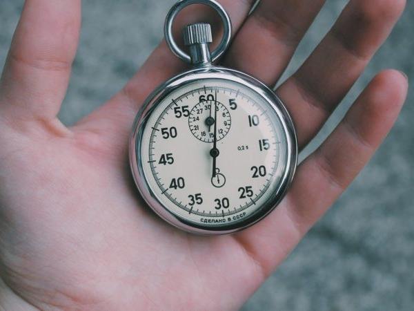A hand holding an pocket-watch style analogue stopwatch