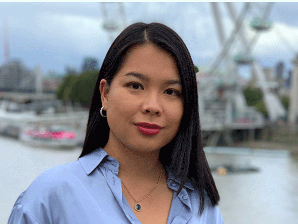 Headshot of student Claudia Juanco. Behind her is a river with boats and a ferris wheel.