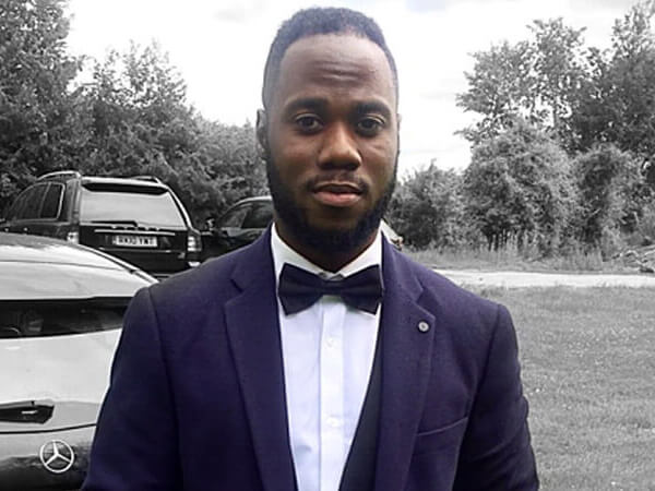 Jesse Koranteng wearing a suit and bow tie and stood in front of a parked Mercedes and Range Rover