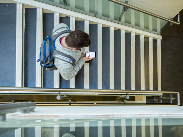 Overhead view of man walking down flight of stairs wearing a backpack and holding mobile phone