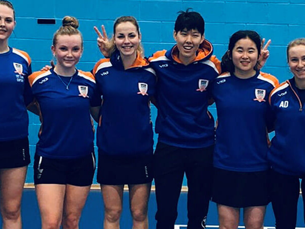 Six Talented Athlete Scholarship Scheme students stood in a line with their arms around each others' shoulders