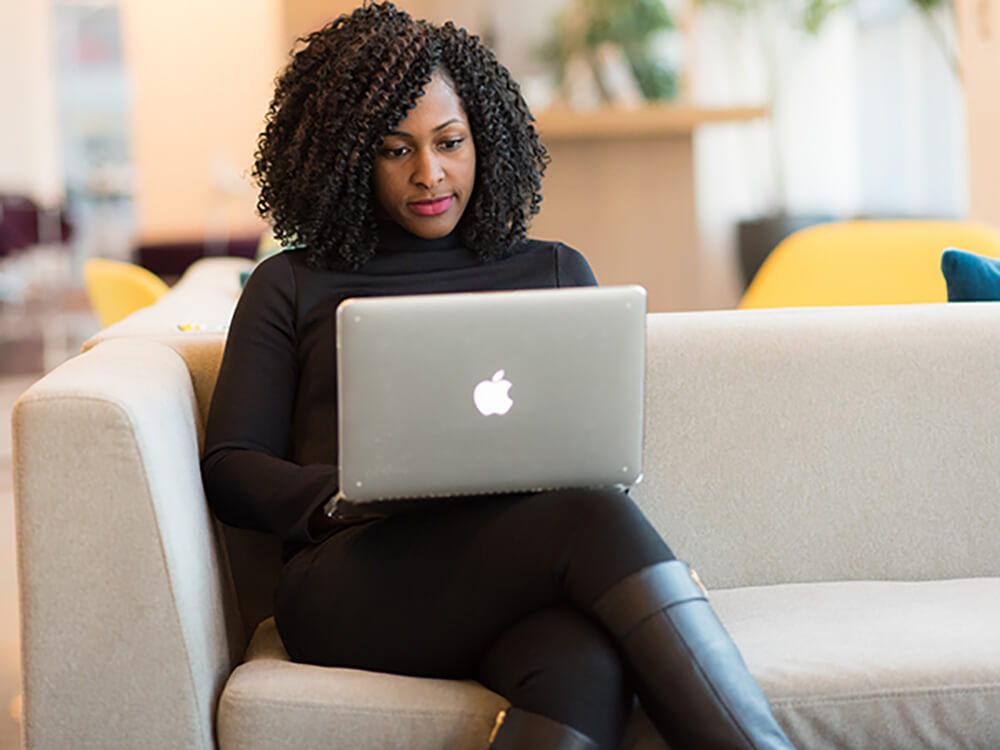 A woman on a sofa using a laptop