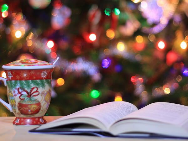 Christmas mug and open book on a table. Multicoloured Christmas tree lights blur in the background.