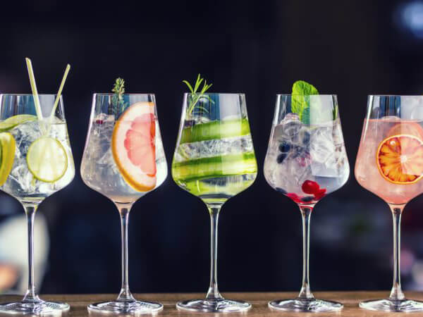 Five glasses of gin and tonic in a row, each with a different garnish - Lemon, grapefruit, cucumber, berries and a mint leaf, orange.