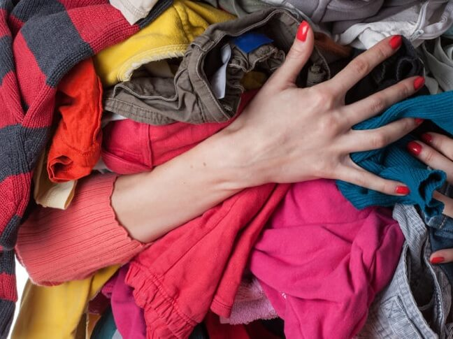 a person holding a pile of coloured clothes