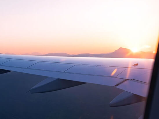 Looking at the sunset through an aeroplane window over a wing