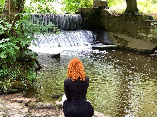 Charlotte sitting at Markeaton park in Derby beside the stream