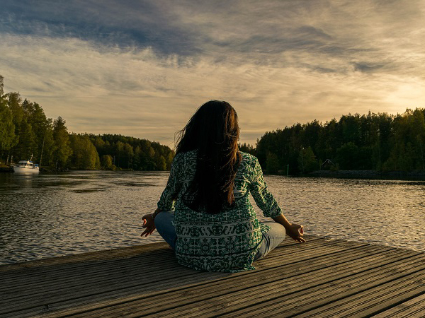 Person sitting cross legged and meditating next to a lake