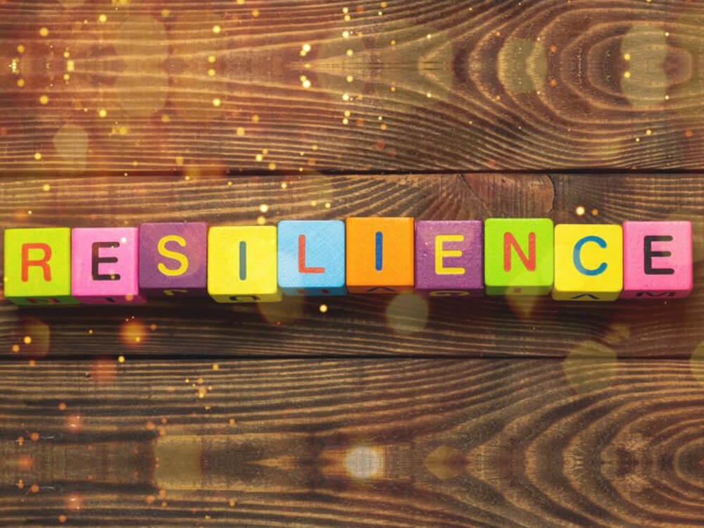Coloured wooden blocks with letters spelling 'RESILIENCE' sit on a wooden background
