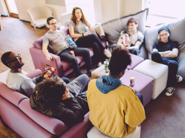 A group of students gathered around a table in a halls common room
