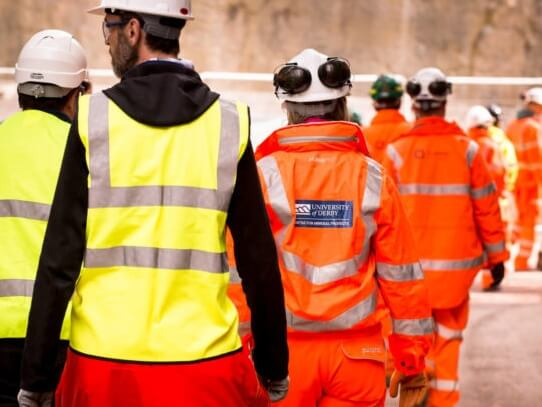 Workers wear hi-vis jackets and hard hats at quarry site