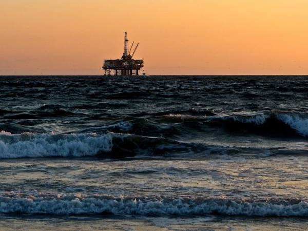 An oil rig at sunset in rough seas
