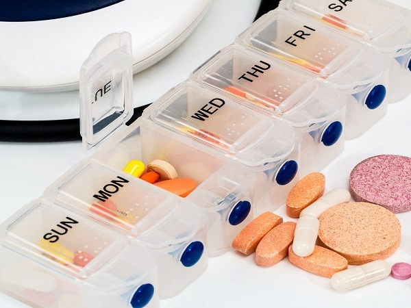 A seven day pill organiser with some tablets